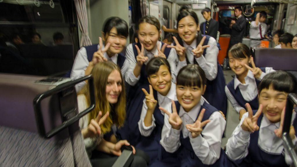 Schülerinnengruppe posiert im Zug in Japan